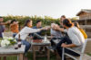 A group of people gathered around an outdoor table enjoying wine